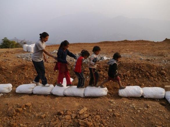 Manisha from the Mountain Fund walks children from Mankhu around the building perimeter.